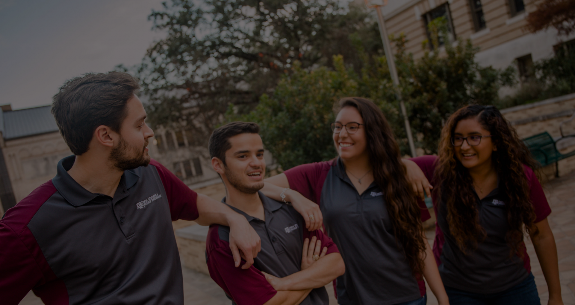 Four student leaders wearing gray and maroon polos stand outside on campus. The photo has a dark gray color overlay.