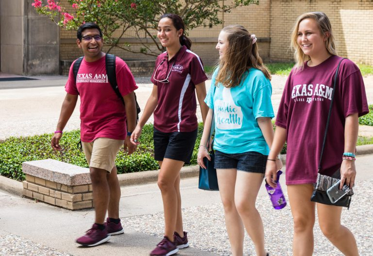 Four students walk on campus smiling