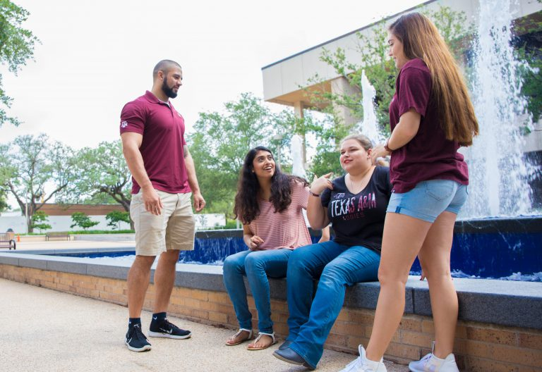 Four students at Rudder Fountain talking; two of the students are sitting on the side of the fountain